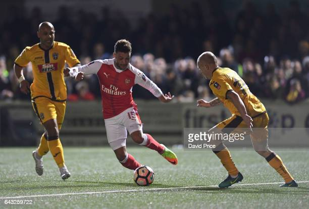 Alex OxladeChamberlain of Arsenal takes on Nicky Bailey and Simon Downer of Sutton during the match between Sutton United and Arsenal on February 20...