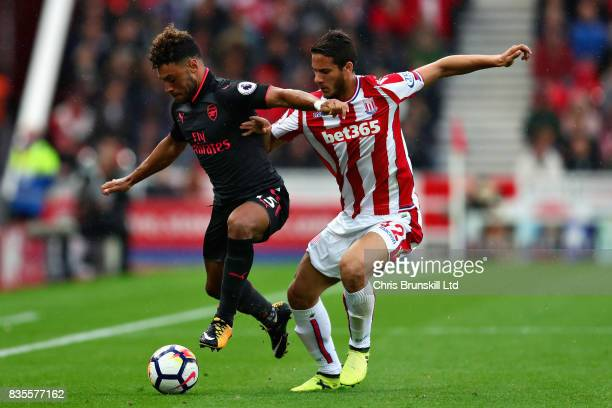 Alex OxladeChamberlain of Arsenal takes on Ramadan Sobhi Ahmed of Stoke City during the Premier League match between Stoke City and Arsenal at Bet365...