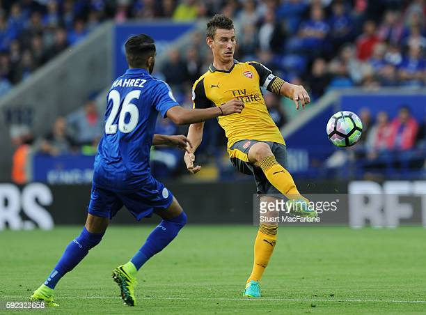 Alex OxladeChamberlain of Arsenal takes on Riyad Mahrez of Leicester during the Premier League match between Leicester City and Arsenal at The King...