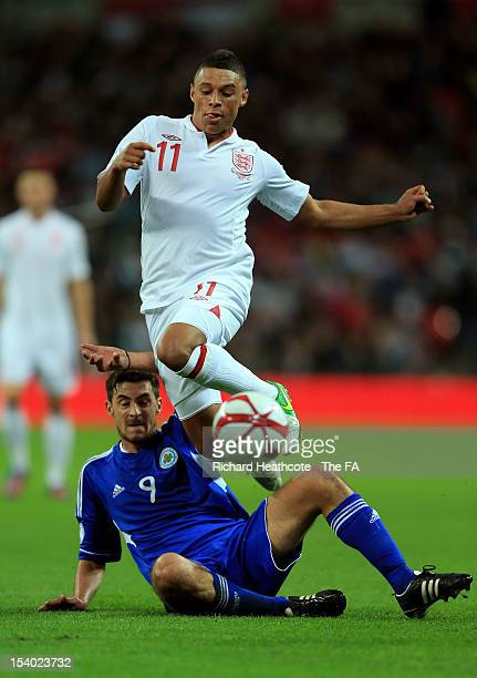 Alex Oxlade-Chamberlain of England hurdles the challenge from Michele Cervellini of San Marino during the FIFA 2014 World Cup Group H qualifying...