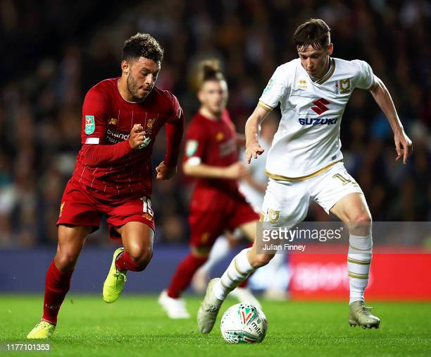 Alex Oxlade-Chamberlain of Liverpool battles for possession with Conor McGrandles of MK Dons during the Carabao Cup Third Round match between Milton...