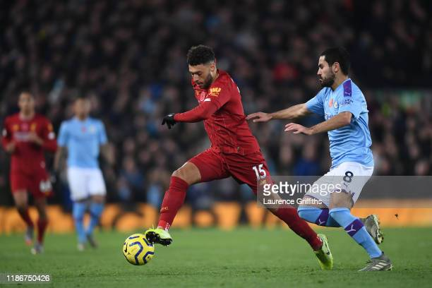 Alex OxladeChamberlain of Liverpool battles for possession with Ilkay Gundogan of Manchester City during the Premier League match between Liverpool...