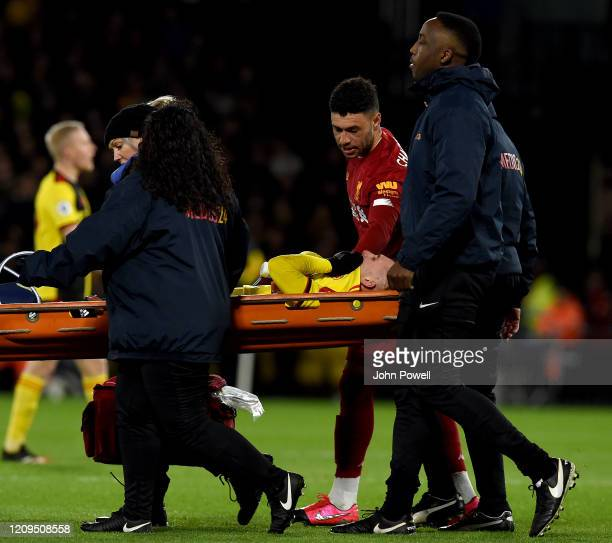 Alex OxladeChamberlain of Liverpool consoles with Gerard Deulofeu of Watford as he is stretchered off with an injury during the Premier League match...