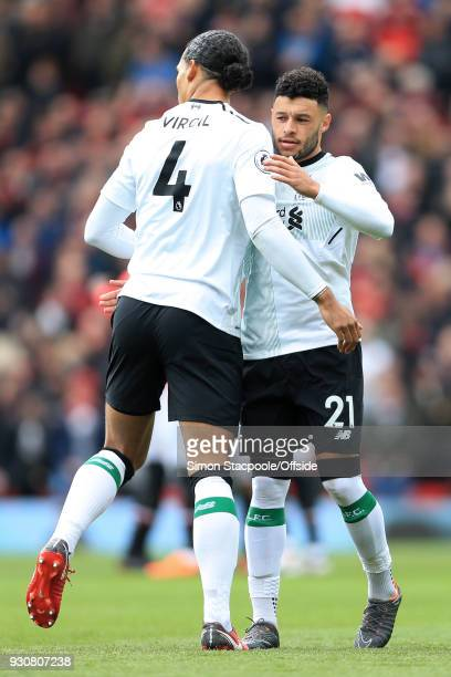 Alex OxladeChamberlain of Liverpool embraces teammate Virgil van Dijk of Liverpool before the Premier League match between Manchester United and...