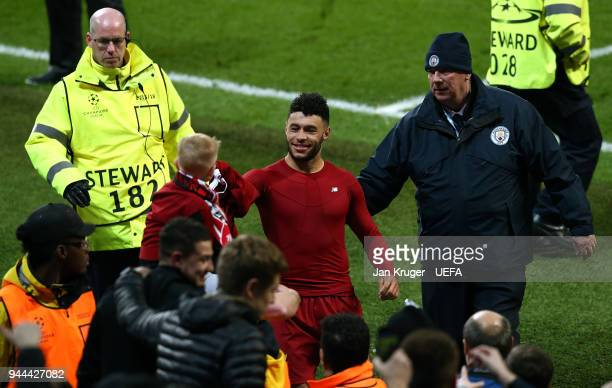 Alex OxladeChamberlain of Liverpool hands his shirt to a young fan after the final whistle during the UEFA Champions League quarter final second leg...