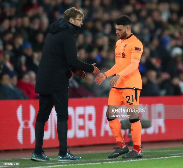 Alex OxladeChamberlain of Liverpool shakes hands with Jurgen Klopp Manager of Liverpool as he is subbed during the Premier League match between...