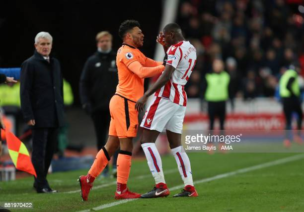 Alex OxladeChamberlain of Liverpool shoves Bruno Martins Indi of Stoke City during the Premier League match between Stoke City and Liverpool at...