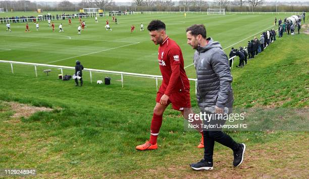Alex OxladeChamberlain of Liverpool walks from the pitch with physio Richie Partridge during the PL2 game at Derby County Training Ground on March 8...
