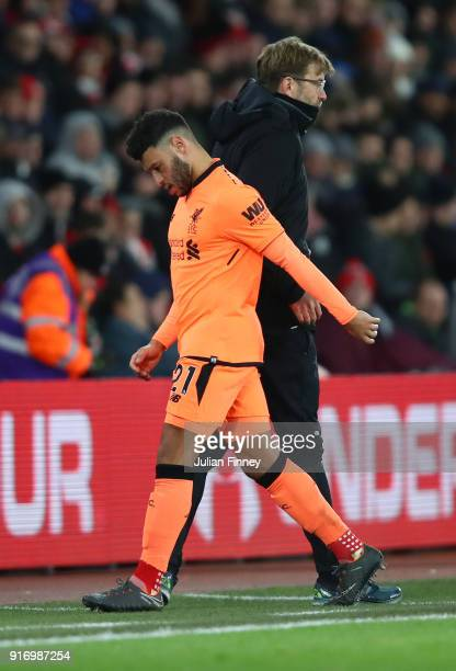 Alex OxladeChamberlain of Liverpool walks past Jurgen Klopp Manager of Liverpool as he is subbed during the Premier League match between Southampton...