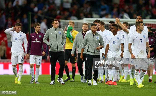 Alex OxladeChamberlain talks to Raheem Sterling of England as the team including Phil Jones and John Flanagan of England walk around the pitch at the...