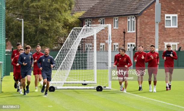 Alex OxladeChamberlain warms up with team mates Jordan Henderson James Milner Alberto Moreno Marko Grujic Andrew Robertson and Jon Flanagan of...