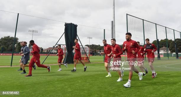 Alex OxladeChamberlain warms up with team mates Jordan Henderson James Milner Alberto Moreno Marko Grujic Andrew Robertson Jon Flanagan and Georginio...