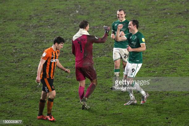 Alex Palmer of Lincoln City is congratulated by team mates Harry Anderson and Tom Hopper after saving a penalty taken by Jordan Flores of Hull City...