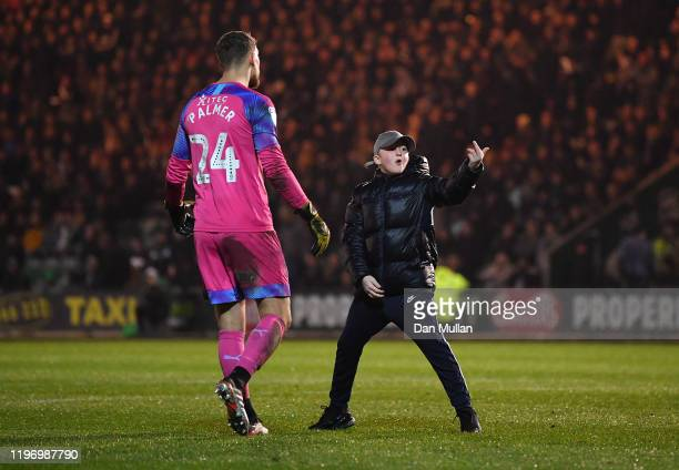 Alex Palmer of Plymouth Argyle ushers away a young pitch invader during the Sky Bet League Two match between Plymouth Argyle and Swindon Town at Home...