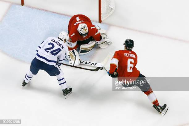 Alex Petrovic assists goaltender Roberto Luongo the Florida Panthers defend the net against a shot by Kasperi Kapanen of the Toronto Maple Leafs...