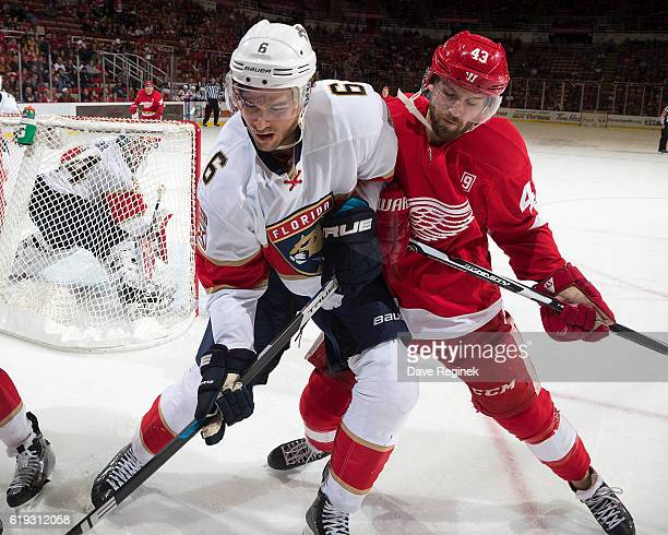 Alex Petrovic of the Florida Panthers and Darren Helm of the Detroit Red Wings battle behind the net during an NHL game at Joe Louis Arena on October...