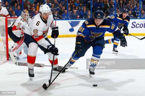 Alex Petrovic of the Florida Panthers and Vladimir Tarasenko of the St Louis Blues fight for control of the puck at the Scottrade Center on February...