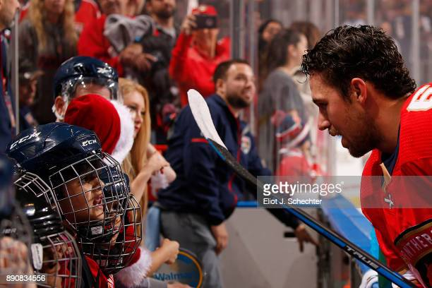 Alex Petrovic of the Florida Panthers chats with hockey fans sitting on the bench for warm ups prior to the start of the game against the Colorado...