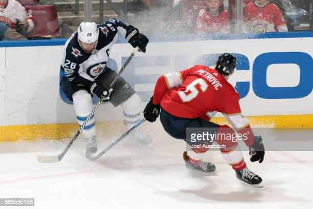 Alex Petrovic of the Florida Panthers defends against Blake Wheeler of the Winnipeg Jets during third period action at the BBT Center on December 7...