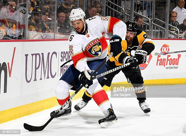 Alex Petrovic of the Florida Panthers handles the puck in front of Phil Kessel of the Pittsburgh Penguins at PPG Paints Arena on October 25 2016 in...