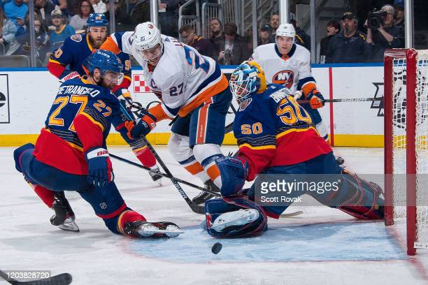 Alex Pietrangelo of the St Louis Blues and Jordan Binnington of the St Louis Blues defend the net against Anders Lee of the New York Islanders at...
