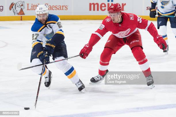 Alex Pietrangelo of the St Louis Blues reaches for the puck with Anthony Mantha of the Detroit Red Wings during an NHL game at Little Caesars Arena...