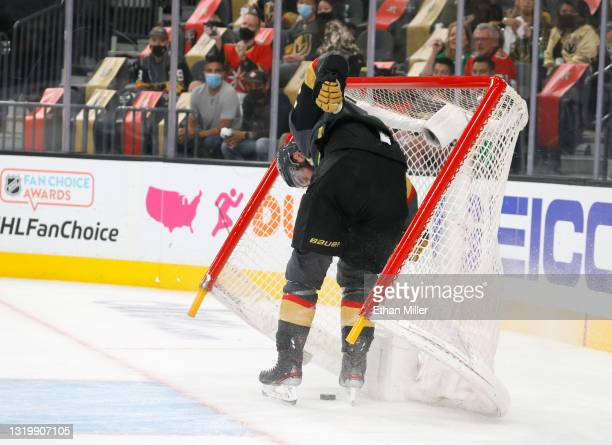 Alex Pietrangelo of the Vegas Golden Knights crashes into and upends the net as he unsuccessfully tries to catch up to a shot on an empty net by Nico...