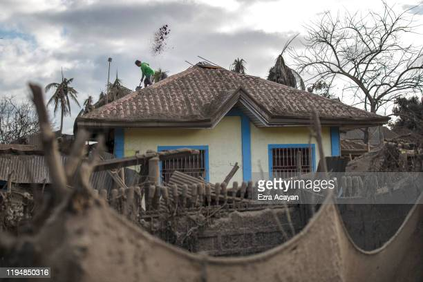 Alex Polopot cleans the roof of his house covered in volcanic ash from Taal Volcano's eruption on January 20 2020 in the village of Buso Buso Laurel...