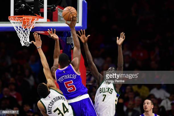 Alex Poythress of the Philadelphia 76ers drives on Giannis Antetokounmpo and Thon Maker of the Milwaukee Bucks as TJ McConnell of the Philadelphia...