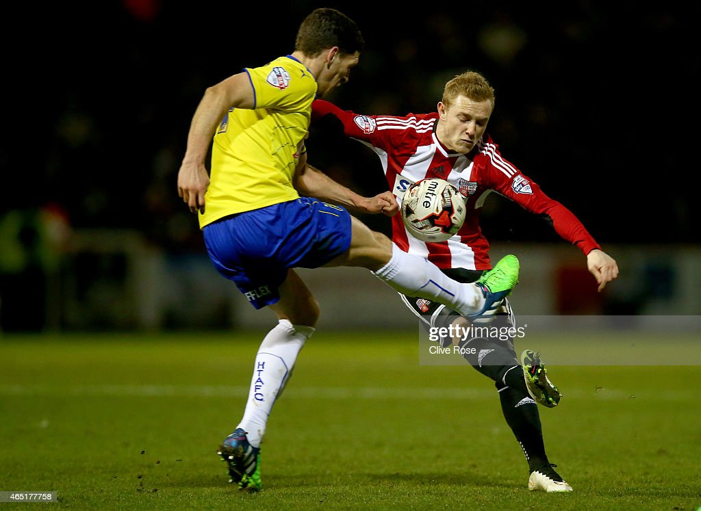 Alex Pritchard of Brentford is challenged by Mark Hudson of Huddersfieldl during the Sky Bet Championship match between Brentford and Huddersfield Town at Griffin Park on March 3, 2015 in Brentford, England.