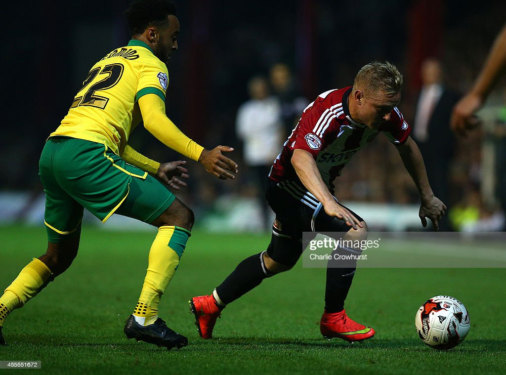 Alex Pritchard of Brentford looks to get away from Norwich's Nathan Redmond during the Sky Bet Championship match between Brentford and Norwich City at Griffin Park on September 16, 2014 in Brentford, England.