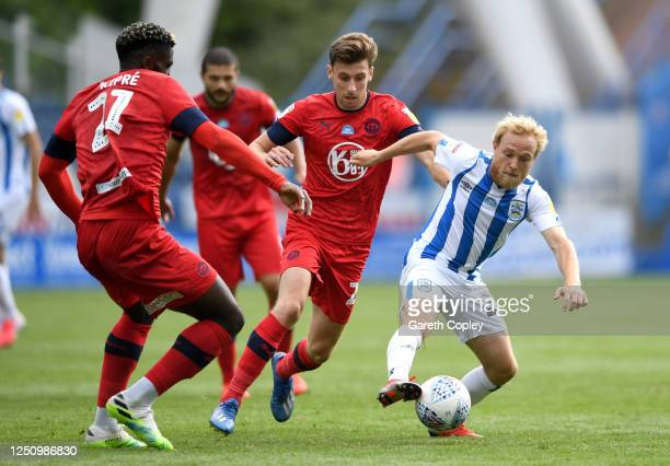 Alex Pritchard of Huddersfield gets past Cedric Kipre and Joe Williams of Wigan during the Sky Bet Championship match between Huddersfield Town and...