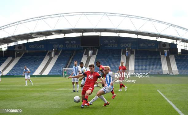 Alex Pritchard of Huddersfield has a shot blocked by Joe Williams of Wigan during the Sky Bet Championship match between Huddersfield Town and Wigan...