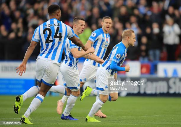 Alex Pritchard of Huddersfield Town celebrates after scoring his team's first goal with his team mates during the Premier League match between...