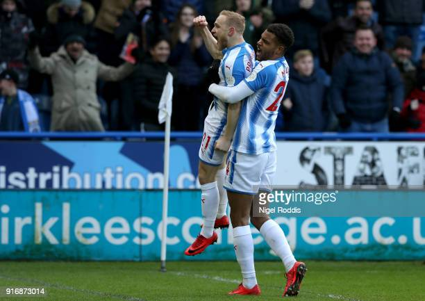 Alex Pritchard of Huddersfield Town celebrates with teammate Steve Mounie after scoring his sides first goal during the Premier League match between...