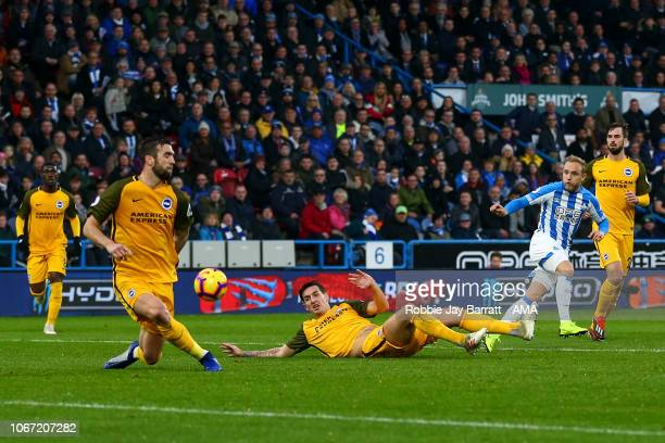 Alex Pritchard of Huddersfield Town has a shot blocked by Shane Duffy of Brighton and Hove Albion during the Premier League match between...