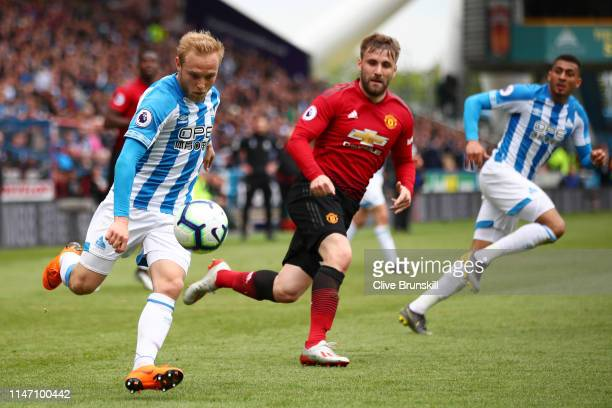 Alex Pritchard of Huddersfield Town is chased by Luke Shaw of Manchester United during the Premier League match between Huddersfield Town and...