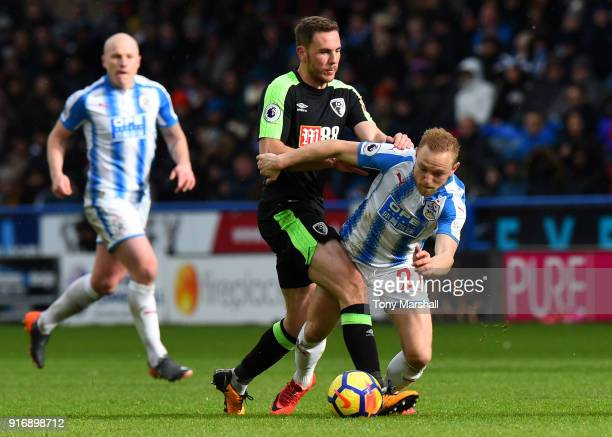 Alex Pritchard of Huddersfield Town is is challenged by Dan Gosling of AFC Bournemouth during the Premier League match between Huddersfield Town and...