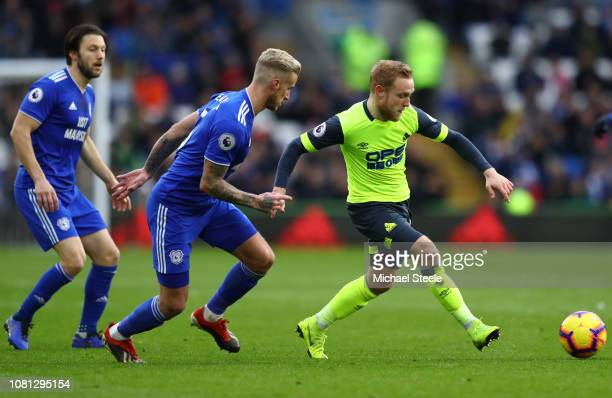 Alex Pritchard of Huddersfield Town is watched by Joe Bennett of Cardiff City during the Premier League match between Cardiff City and Huddersfield...