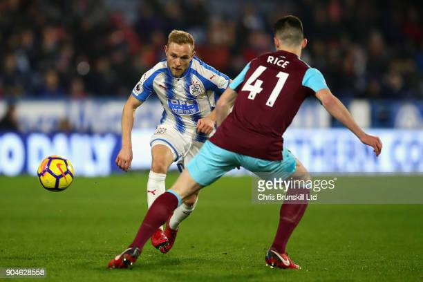 Alex Pritchard of Huddersfield Town plays the ball past Declan Rice of West Ham United during the Premier League match between Huddersfield Town and...