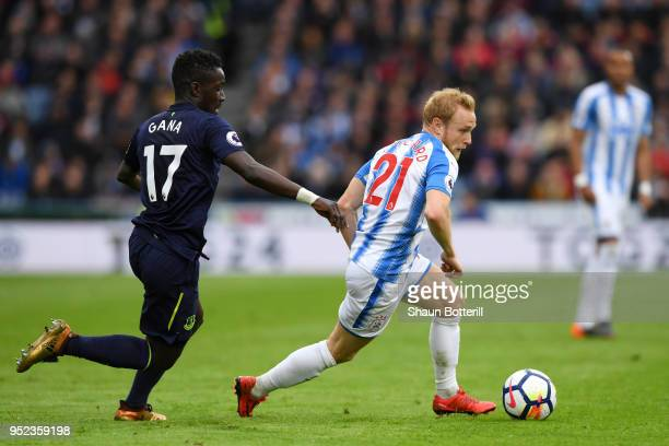 Alex Pritchard of Huddersfield Town runs with the ball under pressure from Idrissa Gueye of Everton during the Premier League match between...