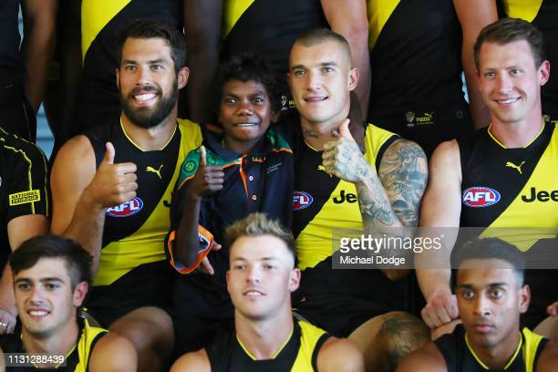 Alex Rance of the Tigers and Dustin Martin of the Tigers pose with a young fan during the AFL Richmond Tigers team photo session at Punt Road Oval on...