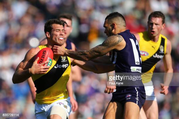 Alex Rance of the Tigers attempts to break from a tackle by Harley Bennell of the Dockers during the round 22 AFL match between the Fremantle Dockers...