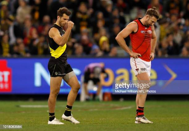 Alex Rance of the Tigers celebrates as Cale Hooker of the Bombers looks dejected after a loss during the 2018 AFL round 22 match between the Richmond...