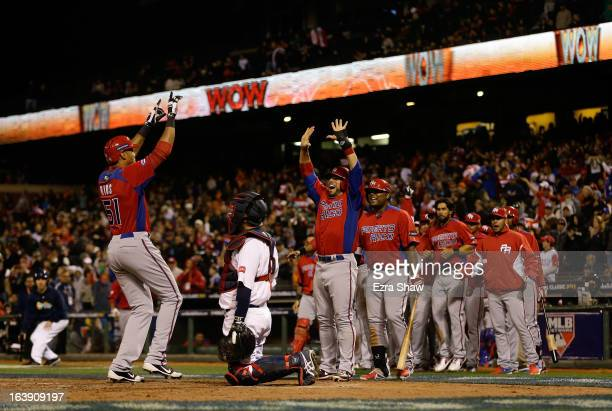 Alex Rios of Puerto Rico is greeted by Mike Aviles and the rest of the Puerto Rico team after he hit a two run home run that scored Aviles in the...