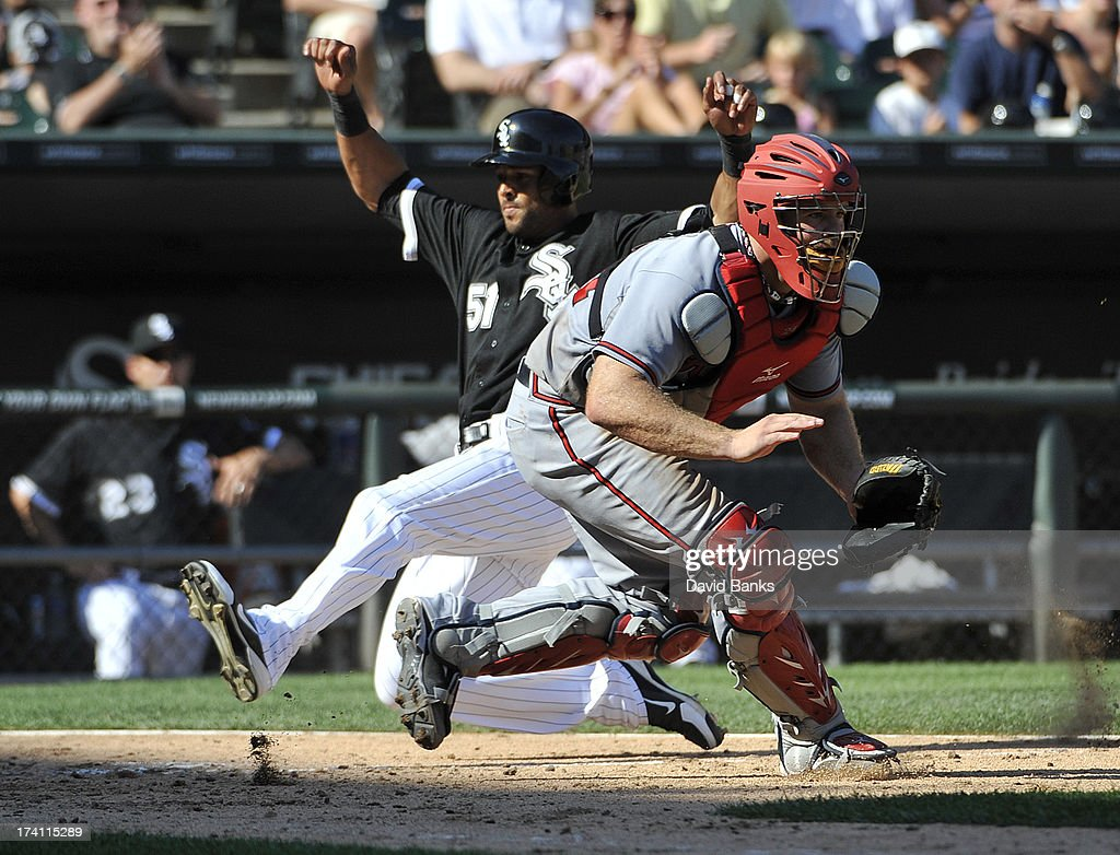 Alex Rios #51 of the Chicago White Sox scores at home as Evan Gattis #24 of the Atlanta Braves stands nearby on July 20, 2013 at U.S. Cellular Field in Chicago, Illinois.