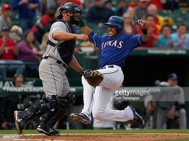 Alex Rios of the Texas Rangers slides into home plate against catcher Michael McKenry of the Colorado Rockies to score in the bottom of the second...