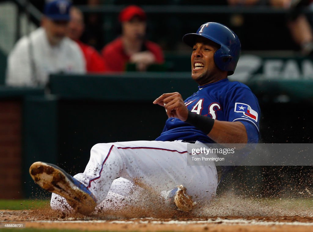 Alex Rios #51 of the Texas Rangers slides into home plate against catcher Michael McKenry #8 of the Colorado Rockies to score in the bottom of the second inning at Globe Life Park in Arlington on May 8, 2014 in Arlington, Texas.