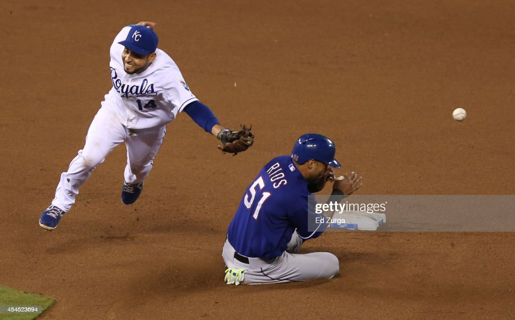 Alex Rios #51 of the Texas Rangers slides into second for a steal as Omar Infante #14 of the Kansas City Royals can't catch the throw from Salvador Perez in the eighth inning at Kauffman Stadium on September 2, 2014 in Kansas City, Missouri.
