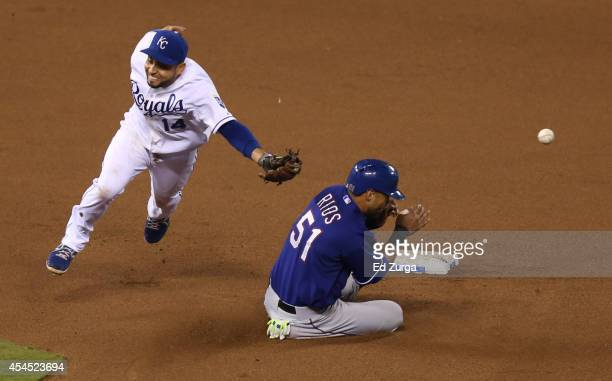 Alex Rios of the Texas Rangers slides into second for a steal as Omar Infante of the Kansas City Royals can't catch the throw from Salvador Perez in...